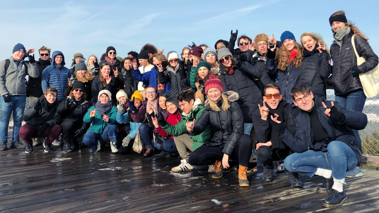 nc-state-prague-group-of-students-doing-the-ncstate-handsign-wolf-ears-winter-time-at the top of lipno tree walk