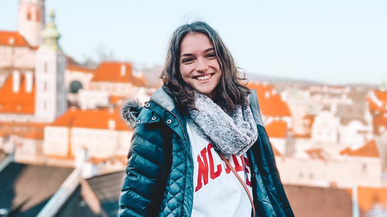 Smiling female student with Cesky Krumlov in the background