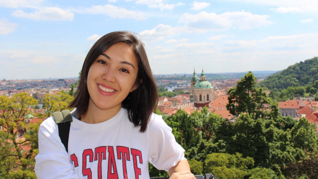 A smiling student with a NC State white t-shirt in front of Prague view