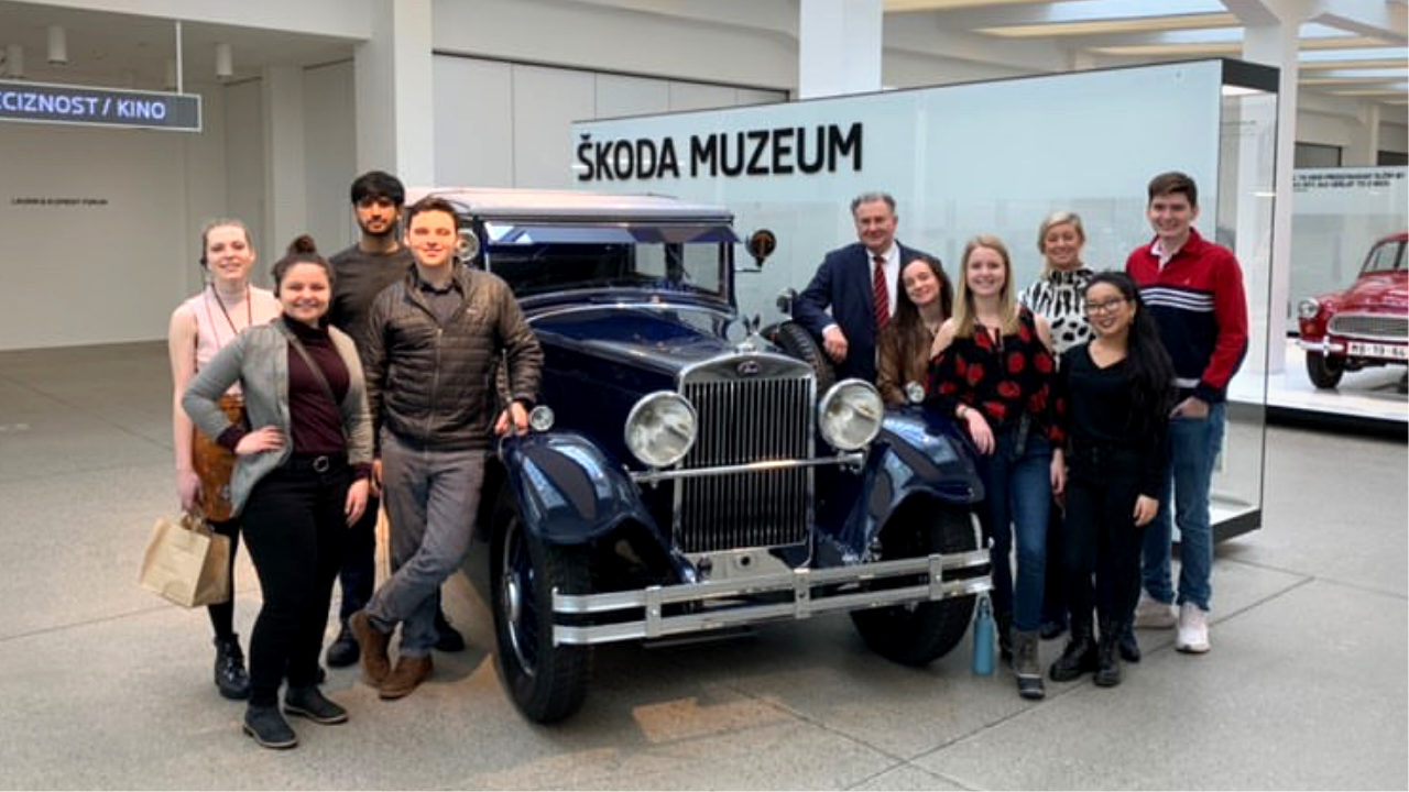 Group of American students smiling around an old Skoda car model at the Skoda car museum
